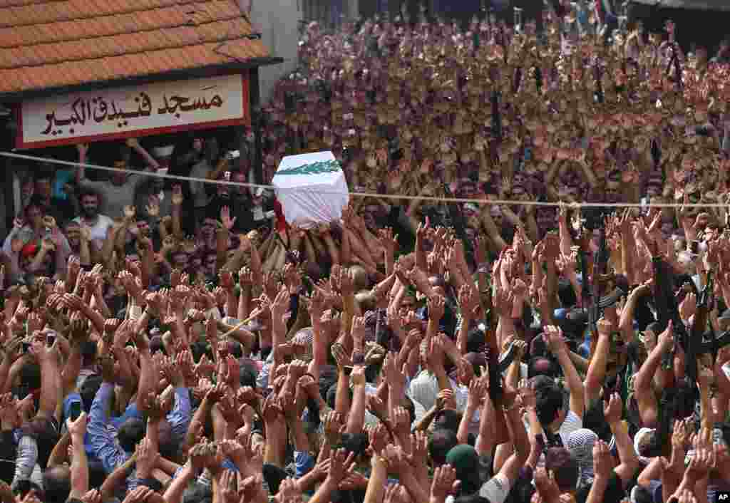Lebanese mourners raise up their hands and weapons as others carry the coffin of Sgt. Ali Sayid who was killed by Islamic militants, during his funeral procession at his home town of Fnaydek, in Akkar north Lebanon.
