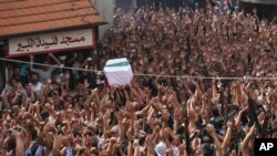 Masyarakat Lebanon mengangkat tangan dan senjata sementara yang lain mengangkat peti jenazah Sersan Ali Sayid yang dibunuh militan ISIS, dalam upacara pemakaman di Akkar, Lebanon (3/9). (AP/Hussein Malla)