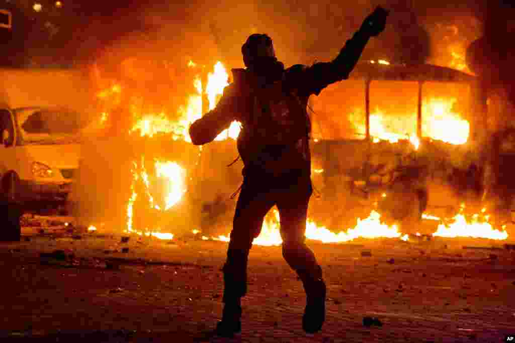 A protester throws a stone towards a burning police bus during clashes with police in central Kyiv, Jan. 19, 2014.