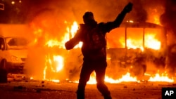 A protester throws a stone towards a burning police bus during clashes with police in central Kiev, Jan. 19, 2014.