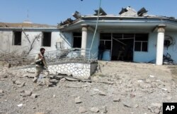 An Afghan security guard inspects the site of a truck bombing attack in Logar province, east of Kabul, Afghanistan, Thursday, Aug. 6, 2015.