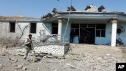 一名阿富汗的保安人员在喀布尔东部的卡车炸弹袭击事件的事发地进行检查(2015年8月6日)。