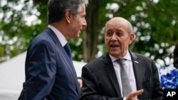 FILE - French Foreign Minister Jean-Yves Le Drian, right, and U.S. Secretary of State Antony Blinken talk during a ceremony at the French ambassador's residence in Washington, July 14, 2021.