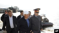 """Tatarstan President Rustam Minnikhanov (2nd R front) walks along the bank of the Volga river during the operation to search for the missing people from the tourist boat """"Bulgaria"""" in Russia's Tatarstan region July 11, 2011."""