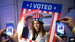 A woman wearing a U.S. patriotic top hat poses for a photograph in the foreground of a cardboard figure depicting Donald Trump Republican presidential candidate during the Election Night Party at the US Embassy in Budapest, Hungary, Nov. 8, 2016.