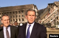 President George W. Bush, accompanied by Secretary of Defense Donald Rumsfeld (L), speaks in front of the west side of the Pentagon on September 12, 2001.