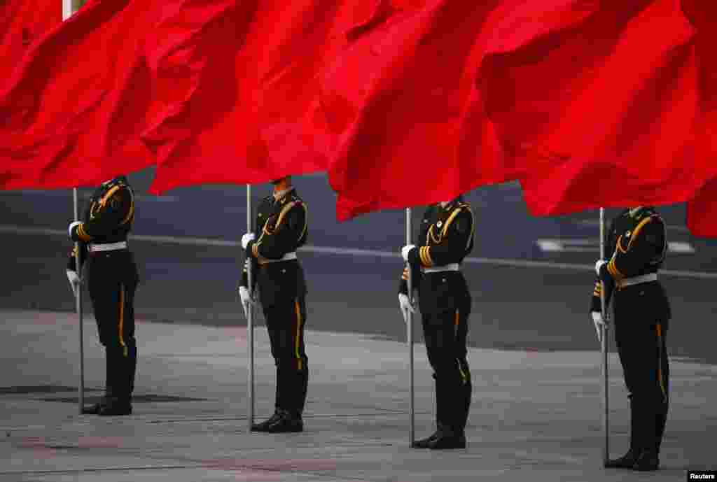 Soldiers of the People's Liberation Army's guard of honor hold flags in front of Beijing's Tiananmen Square during the official welcoming ceremony for Serbian President Tomislav Nikolic outside the Great Hall of the People.