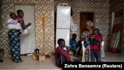Fallou Diop est assis à côté de sa mère Ndeye Boye et de ses frères et soeur, à Niaga, région de Rufisque, au Sénégal, le 28 janvier 2021 (Crédit: REUTERS / Zohra Bensemra)