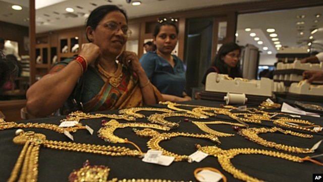 A customer tries on a gold necklace inside a jewellery showroom in the southern Indian city of Hyderabad, April 11, 2012.