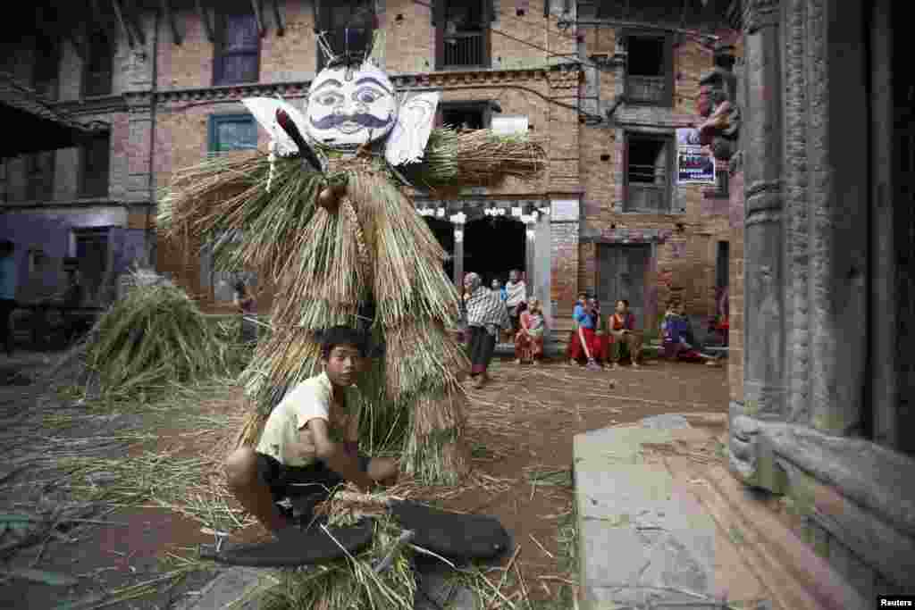 A boy makes an effigy of demon Ghantakarna before it is burned to symbolize the destruction of evil during the Ghantakarna festival at the ancient city of Bhaktapur, Nepal.