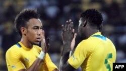 Pierre Emeric Aubameyang (G) na Bruno Ecuele Manga, basani babale ba Gabon, bapesani mbote na match na Sudan na CAN, na Franceville, Gabon, 12 janvier 2021.