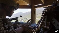 Staff Sergeant Benjamin George, 26, of Kalihi, Hawaii, stands guard in a watchtower at Combat Outpost Pirtle King in Kunar province, Afghanistan, July 6, 2011
