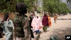 En esta foto tomada el 8 de abril, de 2015, civiles pasan frente a un punto de control del ejército nigeriano en Gwoza, Nigeria, un pueblo recientemente liberado de Boko Haram.