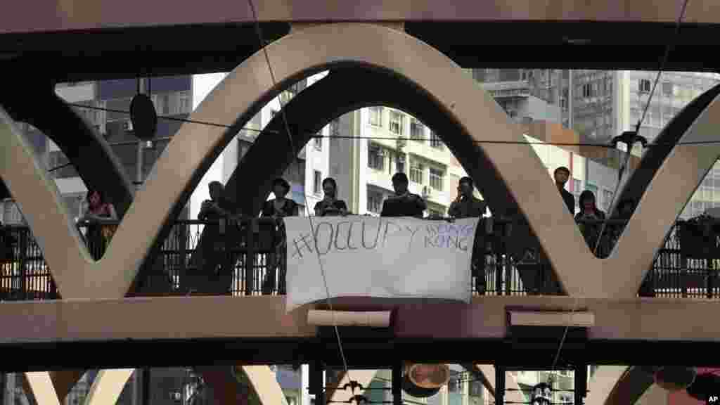 "A banner calling to ""occupy Hong Kong"" hangs from a pedestrian overpass above a sit-in protest in Hong Kong, Sept. 29, 2014."