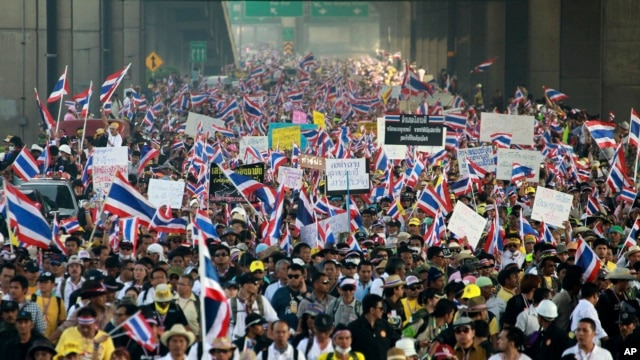 Waving flags and placards, Thai anti-government protesters make their way on a street during a march rally from the government complex on the outskirts of the capital to downtown Bangkok, Thailand, Dec. 9, 2013.