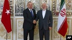 Menlu Turki Mevlut Cavusoglu (kiri) bertemu Menlu Iran Mohammad Javad Zarif di Teheran, hari Rabu (7/2).