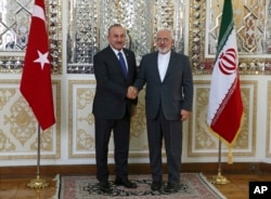 Iranian Foreign Minister Mohammad Javad Zarif, right, and his Turkish counterpart Mevlut Cavusoglu shake hands for journalists at the start of their meeting, in Tehran, Iran, Feb. 7, 2018.