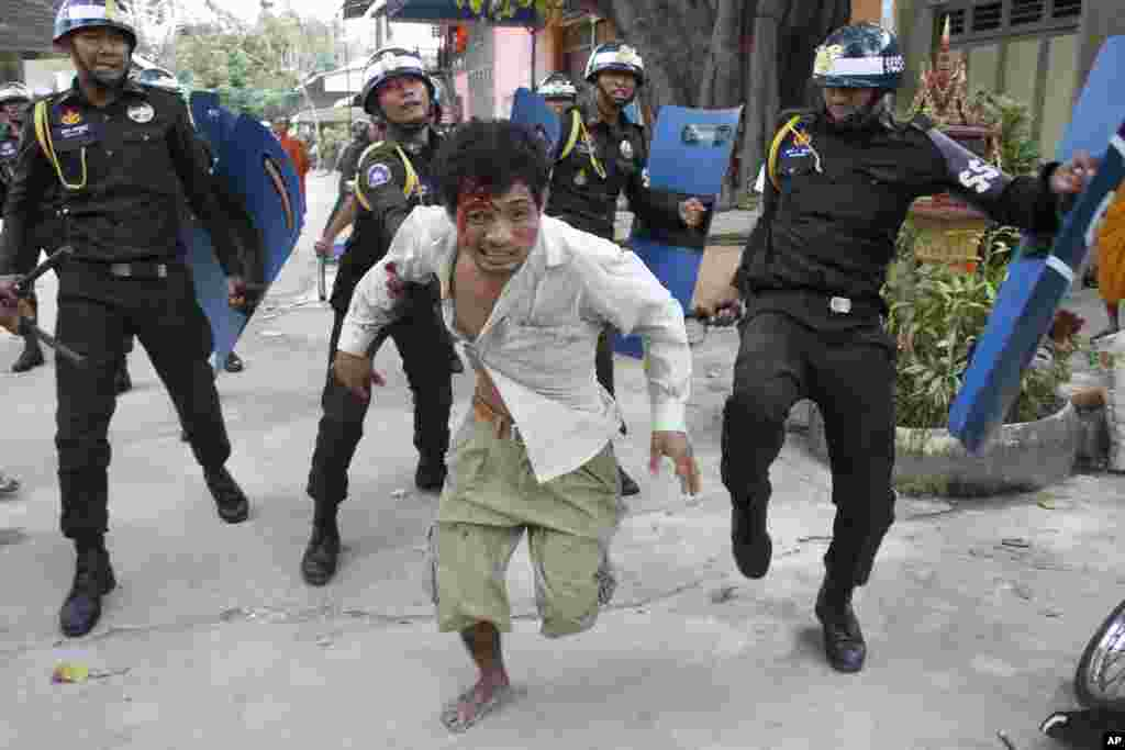 An injured worker escapes from riot police in the compound of a Buddhist pagoda in Phnom Penh, Cambodia, Nov. 12, 2013.