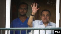 FILE - Ousted President Hosni Mubarak waves to supporters outside his hospital room where he awaits his final retrial for the deaths of hundreds of protesters during the 2011 uprising, Cairo, Oct. 6, 2015. (H.Elrasam/VOA)