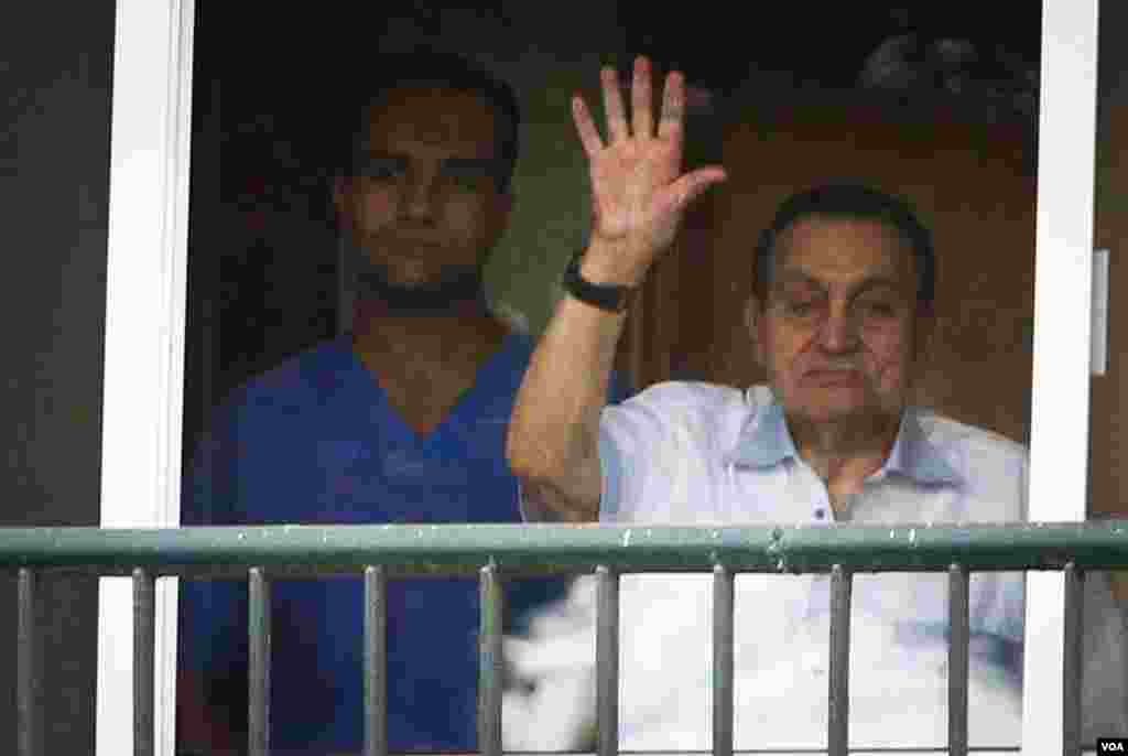Ousted President Hosni Mubarak waves to supporters outside the hospital where he is being treated while he awaits his final retrial for the deaths of hundreds of protesters during the 2011 uprising, Cairo, Oct. 6, 2015. (H.Elrasam/VOA)