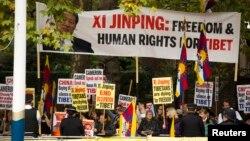 在中国国家主席习近平与英国女王乘坐皇家马车前往白金汉宫的道路旁,人权活动人士举标语牌抗议中国人权 (2015年10月20日)