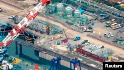 在2013年8月9日從空中拍攝的照片顯示﹐穿著保護服和戴口罩的工人﹐在福島核電廠的工地上正在建立防護堤﹐以防止有放射性的水流入海中