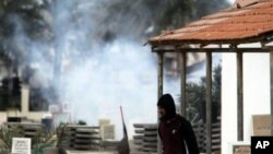 An anti-government protester carrying water to throw on tear gas canisters fired by riot police, moves through a cemetery as gas billows behind him in the Shiite Muslim village of Jidhafs, Bahrain, on the outskirts of the capital of Manama, March 17, 2011