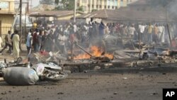 FILE - People gather at the site of a bomb explosion at a road in Kaduna, Nigeria, April 8, 2012.