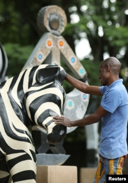 Zimbabwean sculptor Dominic Benhura polishes one of his works at his studio in Harare