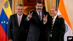 Venezuela's President Nicolas Maduro, center, and Executive Director of Oil and Natural Gas Corporation, Narendra Kumar Verma, flash victory hand signs as they pose for a photo in Caracas, Venezuela, Nov. 4, 2016. At right is PDVSA President Eulogio Del Pino.