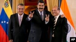 Venezuela's President Nicolas Maduro, center, and Executive Director of Oil and Natural Gas Corporation, el jefe deestado afirmó que solicitó al ministro de Petróleo, Eulogio Del Pino (derecha), tomar acciones legales ante las recientes informaciones que publicó JP Morgan.