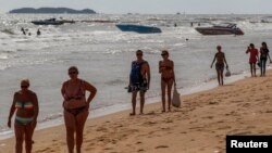 Tourists walk on a beach in Pattaya, June 6, 2014.