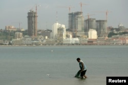FILE - An Angolan fisherman prepares to cast his nets in the bay of Luanda, Jan. 27, 2010.