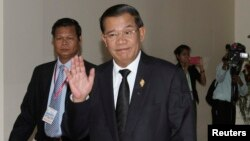 Prime Minister Hun Sen gestures as he arrives at the National Assembly for a meeting in central Phnom Penh, Sept. 24, 2013.