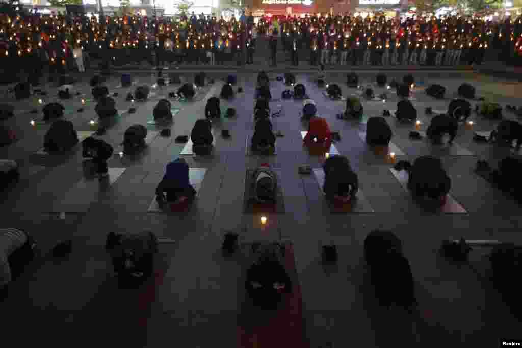 People pray during a candlelight vigil to commemorate the victims of capsized passenger ferry Sewol and to wish for the safe return of missing passengers, in Ansan, Korea, April 23, 2014.