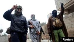 Hombres armados patrullan las calles de Faluya luego de varios días de intensos combates.