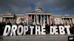Backdropped by Britain's National Gallery in central London, protesters hold placards during a rally to show solidarity with Greece, Sunday, Feb. 15, 2015.