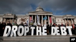 FILE - Protesters hold placards during a rally to show solidarity with Greece in front of Britain's National Gallery in central London, Feb. 15, 2015.