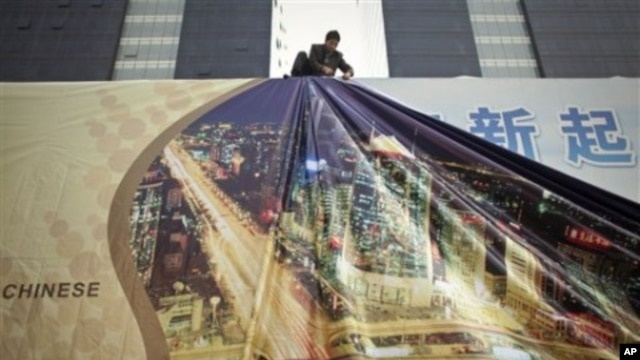 In this 13 Oct 2010 photo, a worker installs a new layer on an advertisement board showing skyscrapers in Beijing's Central Business District, China