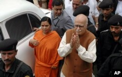 FILE - Indian opposition leader and President of Bharatiya Janta Party (BJP) L.K. Advani, center right, and senior BJP leader Uma Bharti, center left, arrive at a court in Rae Bareilly, in the northern Indian state of Uttar Pradesh.