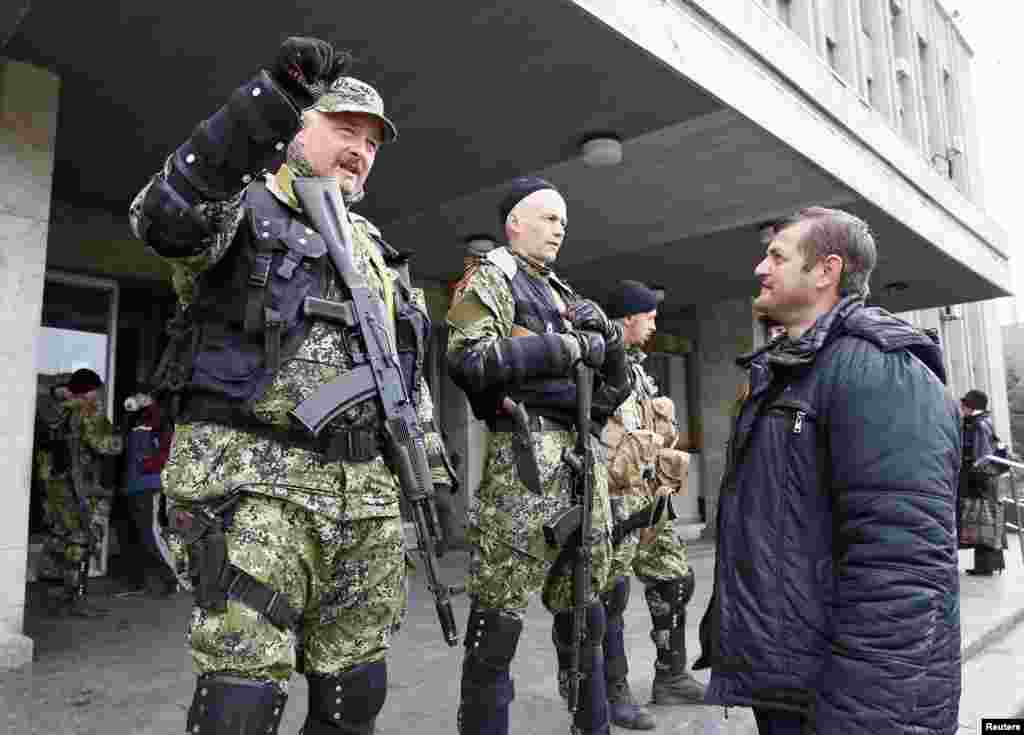 A local resident talks to pro-Russian armed men standing guard outside the mayor's office in Slovyansk, Ukraine, April 14, 2014.