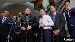 Законодатели-республиканцы беседуют с журналистами у входа в помещение, где должна была дать показания Лора Купер