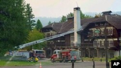 This Sept. 3, 2017 photo provided by the National Park Service shows fire truck positioned outside Lake McDonald Lodge in Glacier National Park, Montana, as firefighters prepare for a blaze that is threatening the century-old Swiss chalet-style hotel.