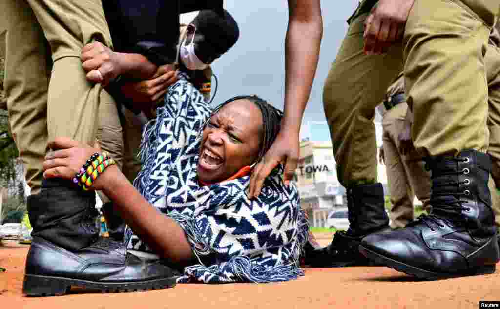 Ugandan academic Stella Nyanzi reacts as police officers detain her for protesting against the way the government gives out food as well as the COVID-19 lockdown situation, in Kampala.