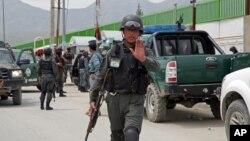Un policía afgano ordena retirarse a periodistas que se apersonaron al hospital Cure, en Kabul.