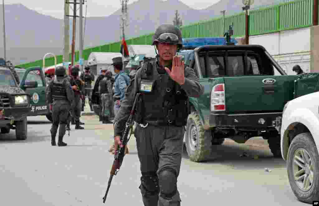 An Afghan policeman prevents journalists from approaching Cure International Hospital in Kabul, Afghanistan, April 24, 2014.