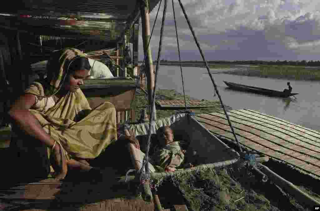 Bà Manira Biwi ngồi gần đứa con mới sanh được một tháng tại một căn lều được dựng tạm tại làng Gagalmari bị lũ lụt thuộc bang Assamm, ngày 2 tháng 7 năm 2012