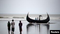 People look at a boat that capsized with a group of Rohingya refugees in it at Bailakhali, near Cox's Bazar, Bangladesh, Oct. 31, 2017.