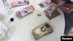 Seorang pelayan restoran menghitung pembayaran menggunakan uang kertas bolivar di Caracas, Venezuela (foto: ilustrasi). Pemerintah Venezuela menarik pecahan uang kertas 100 bolivar.