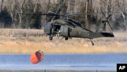 A National Guard helicopter picks up water from a farm pond near Hutchinson, Kansas, March 7, 2017.